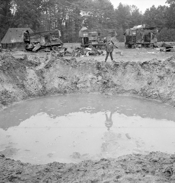 Private S.W. Olive of the 2nd Mobile Laundry and Bath Unit, Royal Canadian Army Ordnance Corps (R.C.A.O.C.), looking into a crater caused by a V-1 flying bomb, which also wrecked the unit's vehicles. Fort de Merxim, Belgium, 15 October 1944.