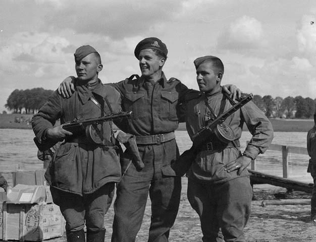 Gunner Brian O'Regan of No. 3 Public Relations Group with two Russian soldiers during the linkup of Russian and American armies at Torgau, Germany, 27 April 1945.