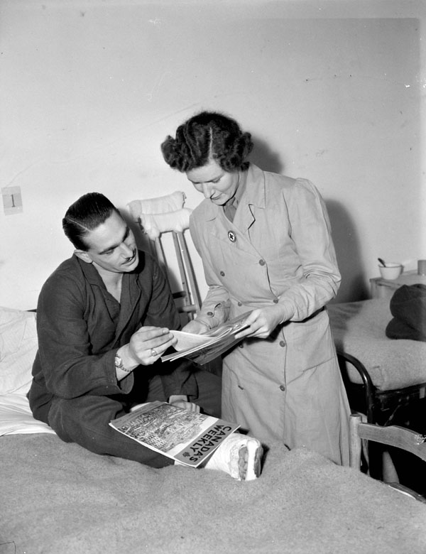 Senior Welfare Officer Dorothy King of the Canadian Red Cross delivering copies of Canada's Weekly to Signalman N.L. Grant at No.2 Canadian General Hospital, Royal Canadian Army Medical Corps (R.C.A.M.C.), Ghent, Belgium, 11 December 1944.