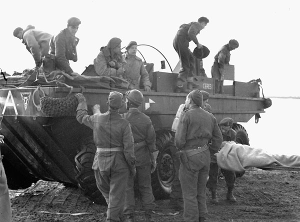 Wounded infantrymen of The North Shore Regiment being carried ashore from a Terrapin amphibious vehicle of the 79th Assault Squadron, Royal Engineers (R.E.) (British Army), west of Terneuzen, Netherlands, 13 October 1944.