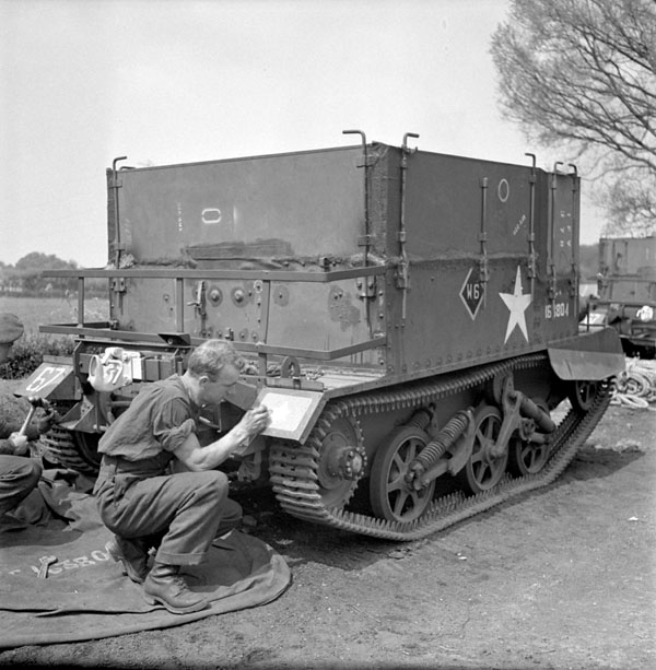 Private J.D. Hamilton stencilling a maple leaf on a Universal Carrier of The Highland Light Infantry of Canada, England, 19 May 1944.