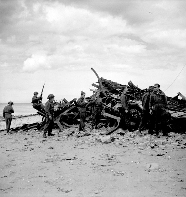 Infantrymen of The Highland Light Infantry of Canada examining the wreckage of the Landing Ship Infantry (LSI) in which they came ashore on D-Day. Normandy, France, ca. 7-8 July 1944.