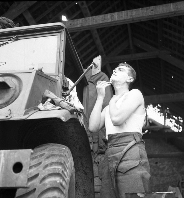 Private H.B. Willis of The Highland Light Infantry of Canada using a truck mirror as a shaving mirror, Vieux Cairon, France, 20 June 1944.