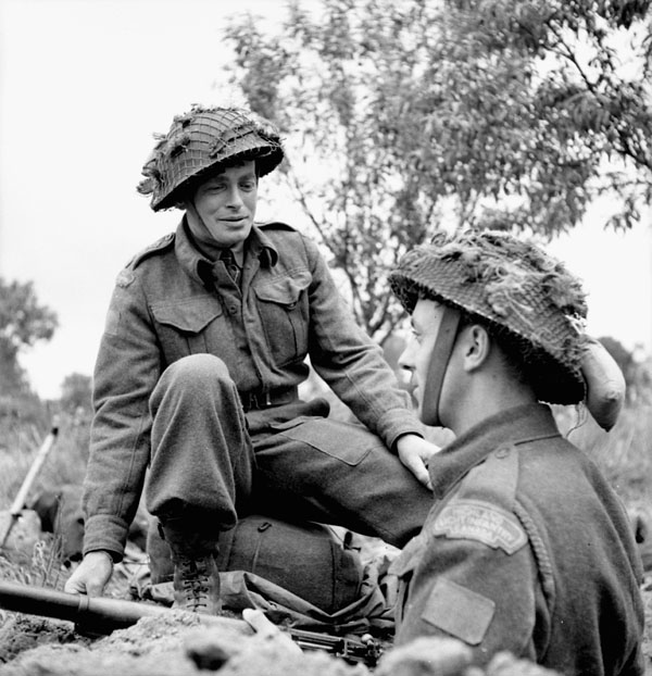H/Captain John M. Anderson, Chaplain of the Highland Light Infantry of Canada, talking with Private Lawrence Herbert in his trench near Caen, France, 15 July 1944.