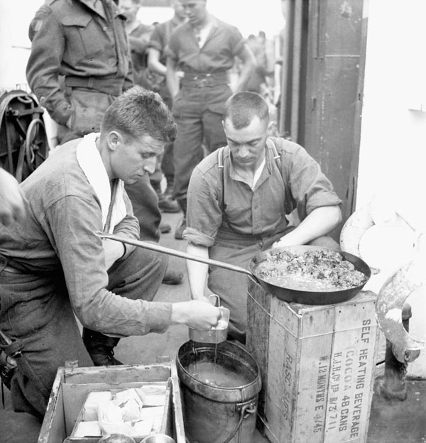 Infantrymen of The Highland Light Infantry of Canada cooking a meal aboard LCI(L) 306 of the 2nd Canadian (262nd RN) Flotilla en route to France on D-Day, 6 June 1944.