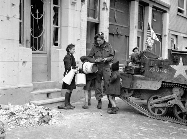 Private R.W. Sisson of the Stormont, Dundas and Glengarry Highlanders talking with Belgian children, Knocke, Belgium, 3 November 1944.