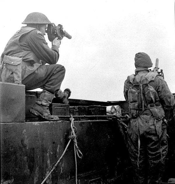Sergeant Hugh H. McCaughey of the Canadian Army Film and Photo Unit filming the advance of The North Shore Regiment across the Scheldt River from the Ayelsche Gat to Eecloo, Netherlands, 11 October 1944.