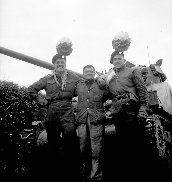 Sergeants C.M. Olson and H.P. Sprague, both of The Calgary Highlanders, with a Dutch civilian, Putte, Netherlands, 6 October 1944.