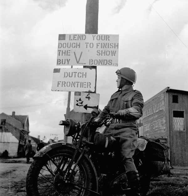 Lance-Corporal J.D. Robillard of The Royal Regiment of Canada passing a sign which reads