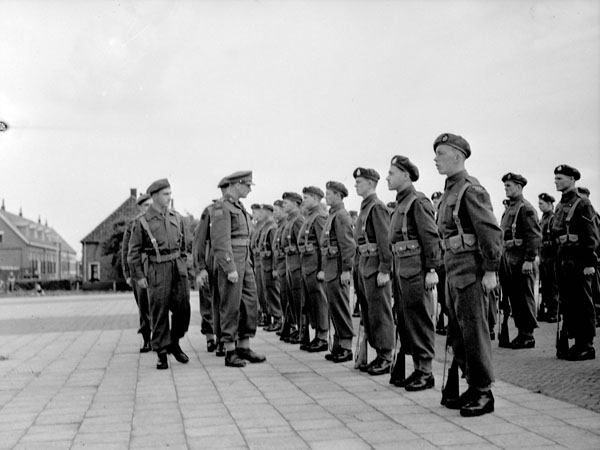 Brigadier J.D.B. Smith inspecting personnel of the 10th Infantry Brigade Workshop, Royal Canadian Electrical and Mechanical Engineers (R.C.E.M.E.), Rijssen, Netherlands, 30 May 1945.
