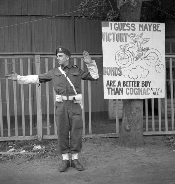 Lance-Corporal P.L. Simpson of No.2 Provost Company, Canadian Provost Corps (C.P.C.), in front of a poster which reads