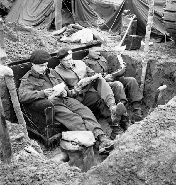 Troopers of The Fort Garry Horse reading mail on a couch in their slit trench in the Hochwald, Germany, 5 March 1945.