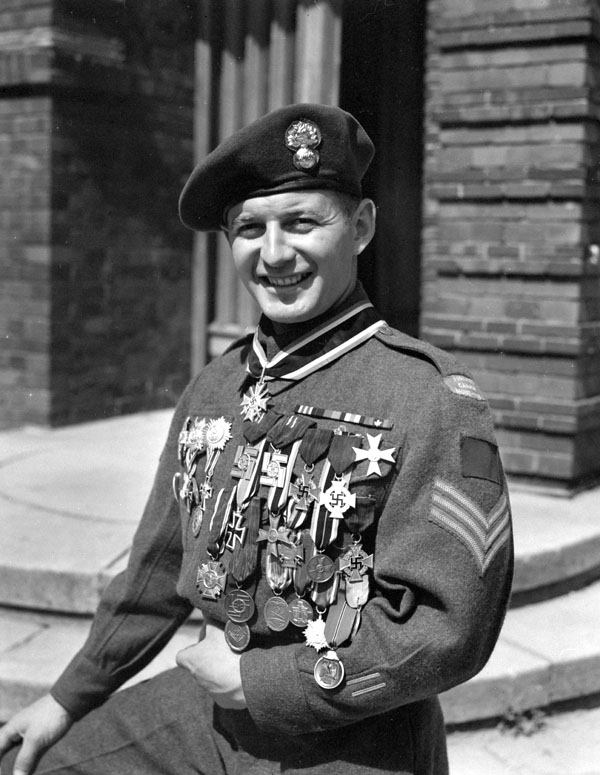 Sergeant G. Durocher of Les Fusiliers Mont-Royal displaying twenty-nine German medals which he acquired as souvenirs, Berlin, Germany, 19 July 1945.