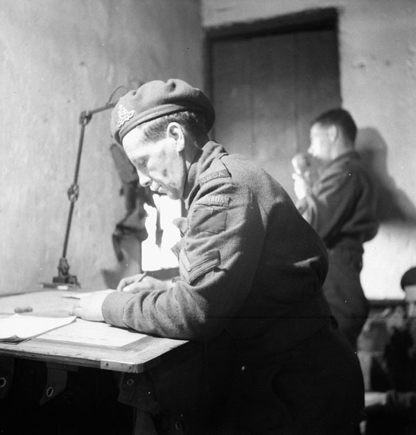 Bombardier M.C. Hughes and Sergeant-Major R.A. Williams of the 4th Field Regiment, Royal Canadian Artillery (R.C.A.), at work in a battery command post, Ossendrecht, Netherlands, 23 October 1944.