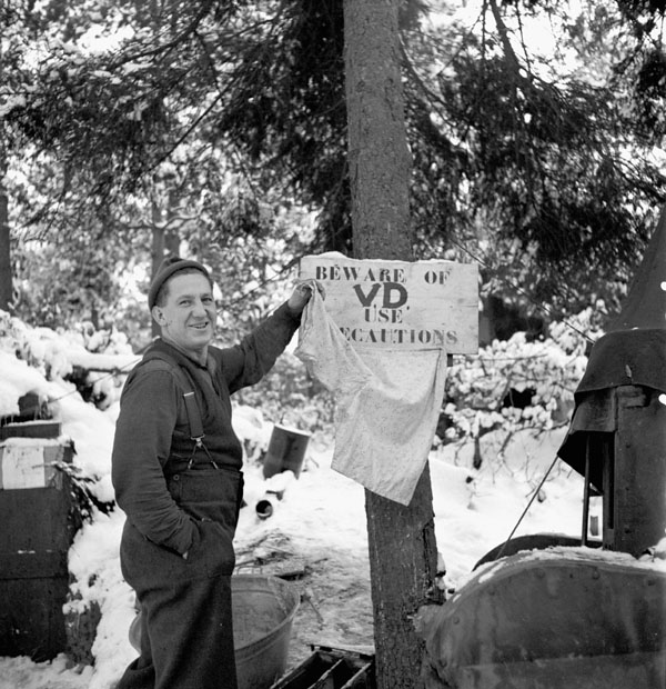 Private Louis Dufour of The Essex Scottish Regiment standing beside a veneral disease warning poster, Groesbeek, Netherlands, 24 January 1945.