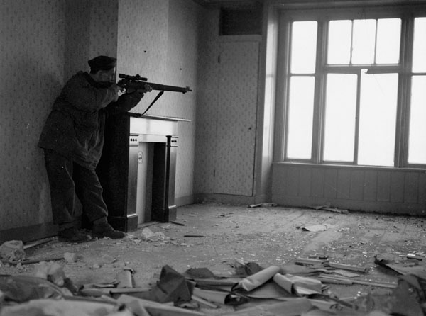 Sniper Arthur Godin of Le Régiment de la Chaudière taking aim from the interior of a building in Zutphen, Netherlands, 7 April 1945.