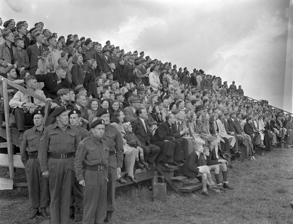 Dutch civilians watching an inspection and marchpast of the 5th Canadian Armoured Division, Eelde, Netherlands, 23 May 1945.