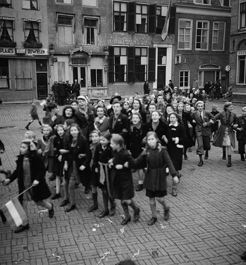 Dutch children dressed in orange paper hats and ribbons to celebrate the 2nd Canadian Infantry Division's liberation of Goes, Netherlands, 30 October 1944.