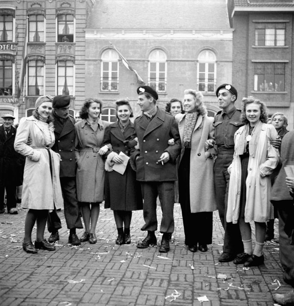 Sergeants R.Y. Williams , J.J. Coghill and W. Anaka, all of The Fort Garry Horse, talking with Dutch women  in the newly-liberated city of Goes, Netherlands, 30 October 1944.
