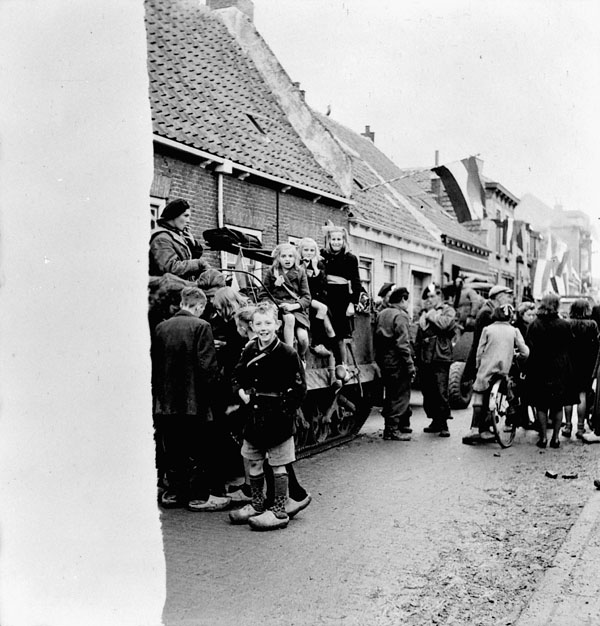 Personnel of  the 14th Canadian Hussars meeting Dutch children during the liberation of Oostkerke, Netherlands, 1 November 1944.
