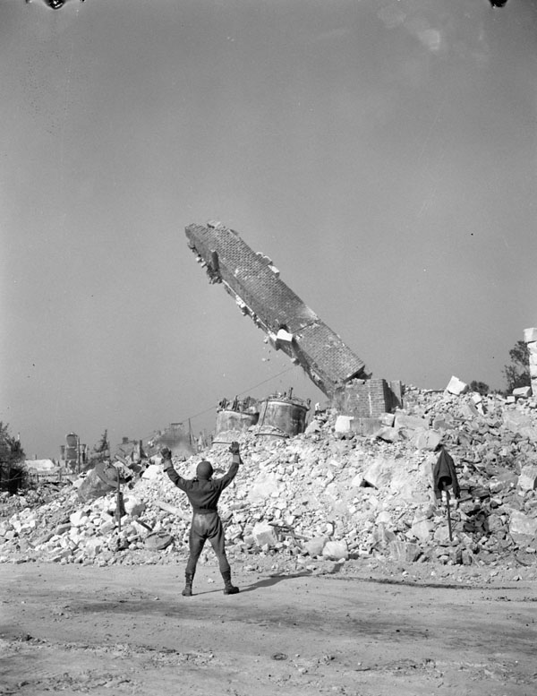 Personnel of the 23rd Field Company, Royal Canadian Engineers (R.C.E.), pulling down  destroyed buildings, Caen, France, 4 August 1944.