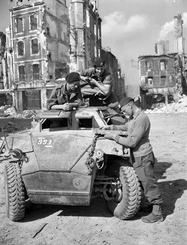 The driver of a Humber I scout car receiving orders, Falaise, France, 17 August 1944.