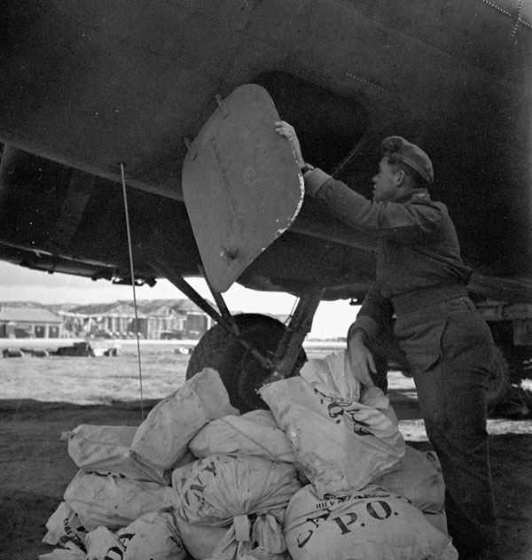 Unloading of the first load of airmail for Canadian soldiers in Italy from a Boeing B-17 aircraft of No.168(HT) Squadron, Royal Canadian Air Force, Foggia, Italy, 30 December 1943.