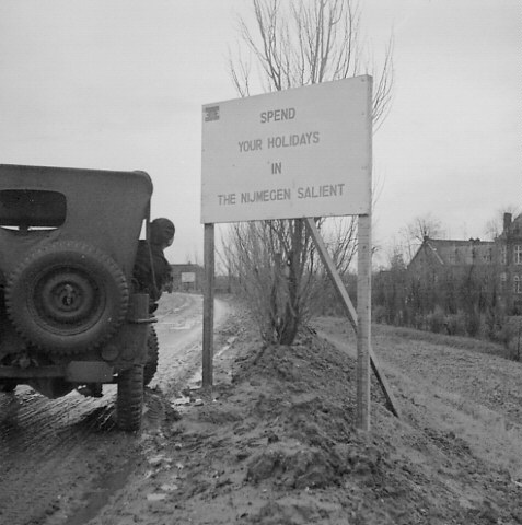 """An unidentified member of the 18th Field Company, Royal Canadian Engineers (R.C.E.), leans out of his jeep to read a sign which states, """"Spend your holidays in the Nijmegen Salient"""", Nijmegen, Netherlands, 24 November 1944."""