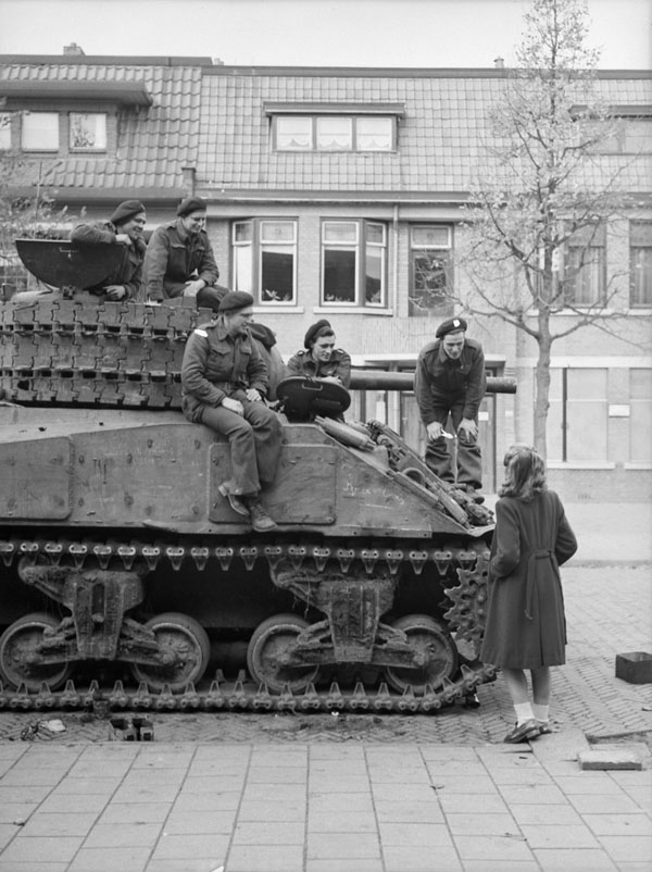 A Dutch girl offering coffee to the crew of a Sherman tank of the South Alberta Regiment, Bergen op Zoom, Netherlands,  29 October 1944.