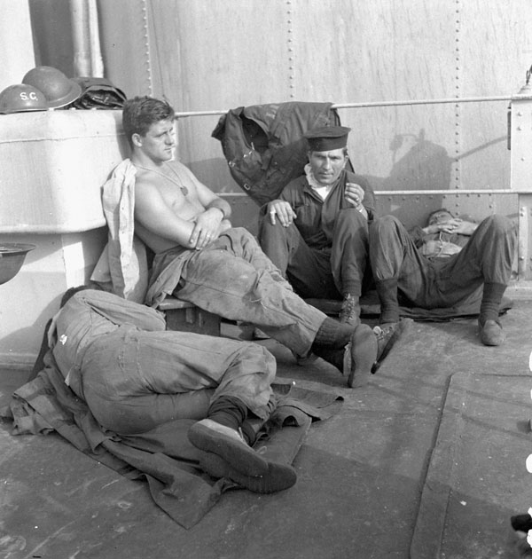 Able Seamen Garth Barnes and Paul Kuzma relaxing during a lull in action stations aboard the cruiser H.M.C.S. UGANDA in the Pacific Ocean, 18 May 1945.