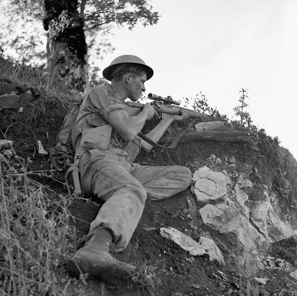 Private J.E. McPhee of The Seaforth Highlanders of Canada, who is armed with a sniper rifle, under German mortar fire, Foiano, Italy, 6 October 1943.