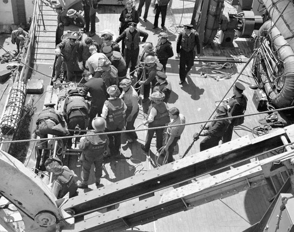 A wounded Royal Navy Beach Commando being taken aboard H.M.C.S. PRINCE DAVID off the Normandy beachhead, France, 6 June 1944.