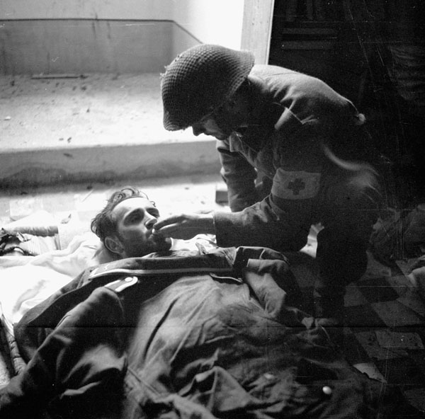 Private B.D. Flynn of the Regimental Aid Party, The Seaforth Highlanders of Canada, giving a drink of water to a badly-wounded German prisoner inside a church, Catona, Italy, 21 December 1943.