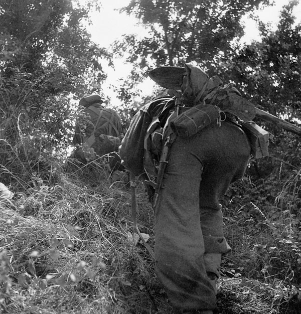 Infantrymen of the Highland Light Infantry of Canada advancing towards Vaucelles, France, 18 July 1944.