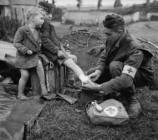 Lance-Corporal W.J. Curtis of the Royal Canadian Army Medical Corps (R.C.A.M.C.) bandages the burnt leg of a French boy whose brother looks on, Boissons, France, 19 June 1944.
