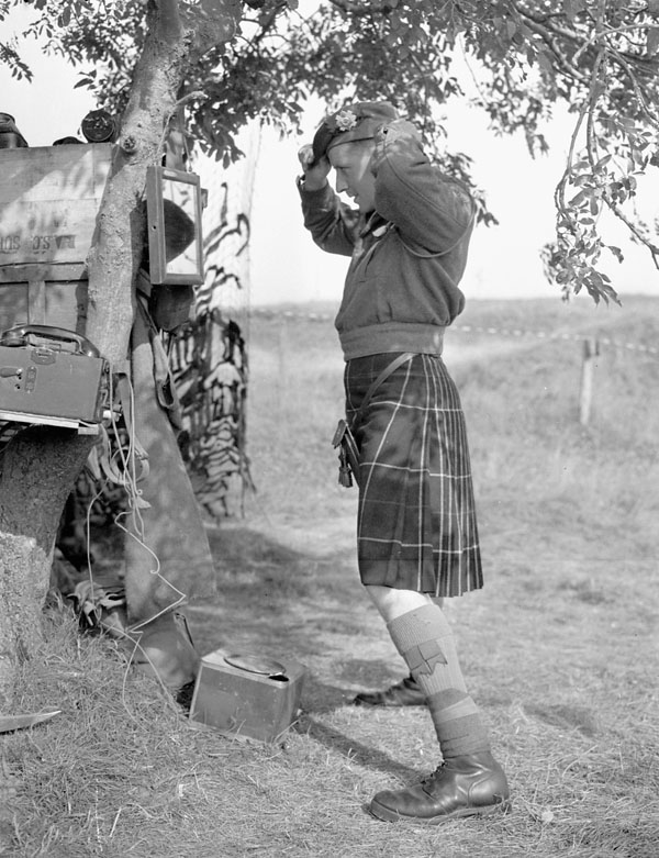 Captain Peter K. Kennedy, a company commander of The Highland Light Infantry of Canada, dressing for Sunday dinner, Thaon, France, 6 August 1944.