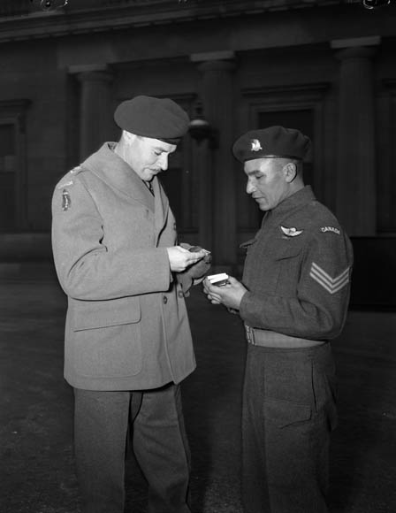 "Lieutenant-Colonel J.F.R. Akehurst, Commanding Officer,  2nd Battalion, First Special Service Force, examines Sergeant Tommy Prince's Military Medal, which was awarded  for ""distinguished and gallant service"" at Anzio. Buckingham Palace, London, England, 12 February 1945."