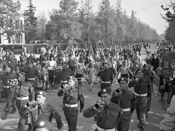 The bugle band of the Royal Canadian Regiment  parading through the liberated city of Apeldoorn, Netherlands, ca. 17-18 April 1945.