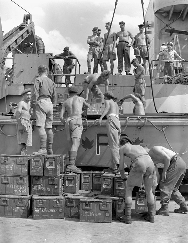 Commandos loading ammunition aboard a Landing Craft Assault (LCA) of H.M.C.S. PRINCE DAVID near Taranto, Italy, 13 September 1944.