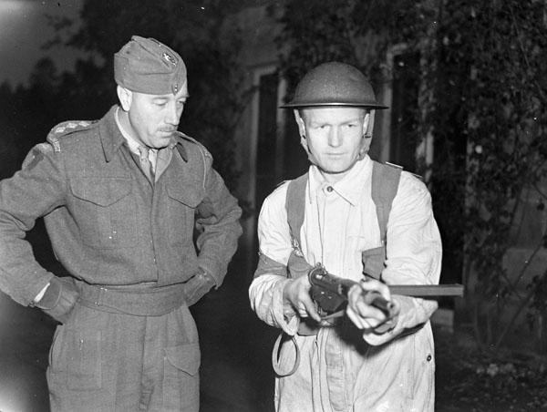 Captain Lyle Monk of The Algonquin Regiment watches Corporal Jack Richmond demonstrate the handling of a Sten light machine gun at the regiment's barracks, England, 22 November 1943.