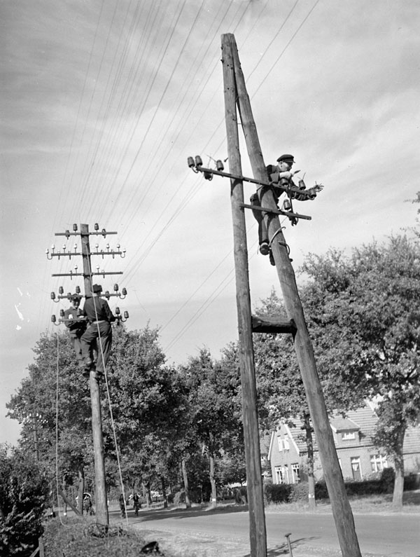 Personnel of the 7th Infantry Brigade (Rifles), Canadian Army Occupation Force (C.A.O.F.), repairing telephone lines, Aurich, Germany, 12 August 1945.