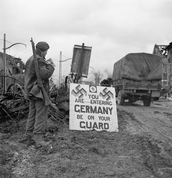"""Corporal Urban Mayo of the 13th Field Company, Royal Canadian Engineers (R.C.E.), reading a sign which states, """"You are entering Germany - Be on your guard"""", Wyler, Germany, 9  February 1945."""