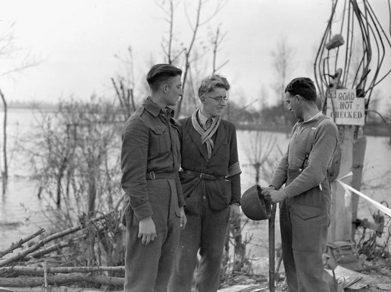Sapper A.T. White  of the Royal Canadian Engineers (R.C.E.), 3rd Canadian Infantry Division, talking with members of the Dutch Resistance near the Belgium-Netherlands border, 16 October 1944.