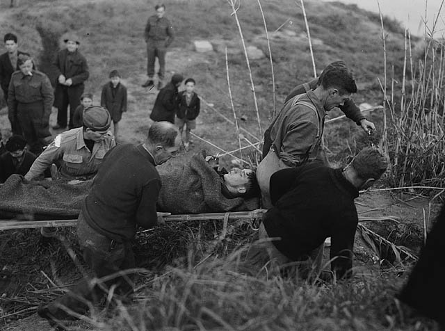 Personnel of the 1st Canadian Armoured Brigade carrying Lieutenant Harold Hanreck of the United States Army Air Corps on a stretcher after his aircraft crashed into the Adriatic Sea. San Vito di Ortona, Italy, 31 December 1943.