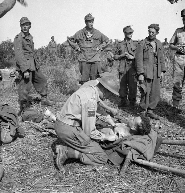 Captain J.A. Gardner talking with a wounded German soldier in the Liri River valley, Italy, 24 May 1944.