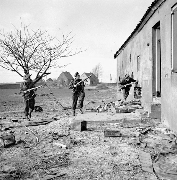 Infantrymen of The Queen's Own Cameron Highlanders of Canada entering a house on the south bank of the Rhine River, Germany, 18 March 1945.