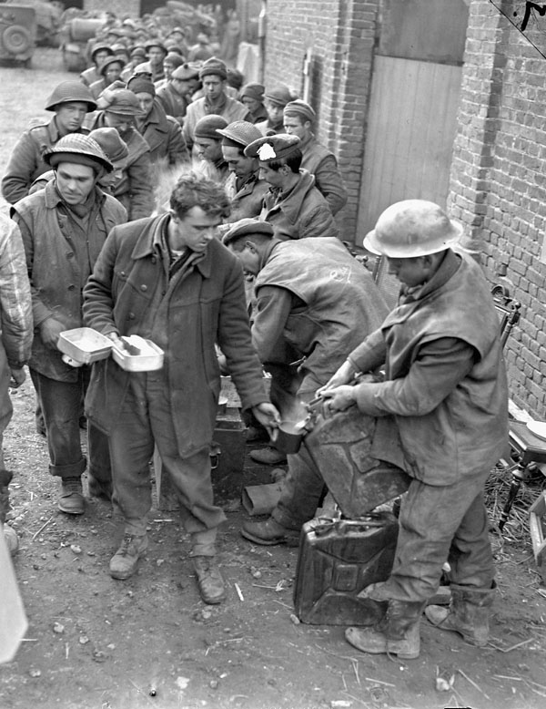 Infantrymen of the Argyll and Sutherland Highlanders of Canada eating dinner in a barnyard, Veen, Germany, 7 March 1945.