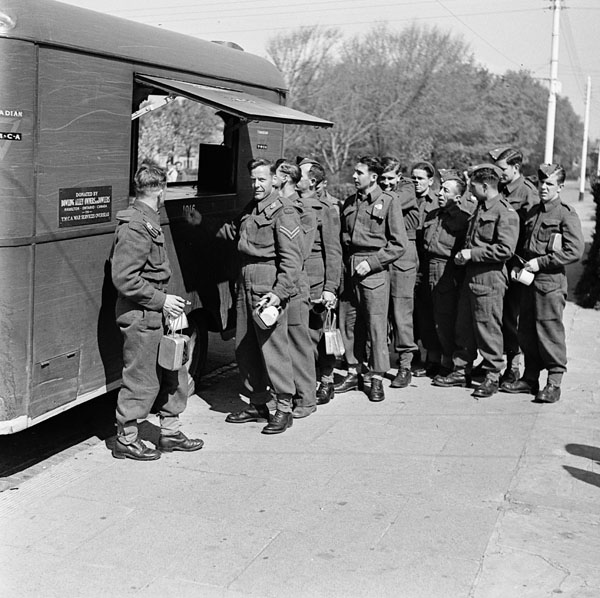 Soldiers of the Royal Regiment of Canada queuing up at a Canadian Y.M.C.A. War Services Overseas refreshment van, England, 19 April 1943.