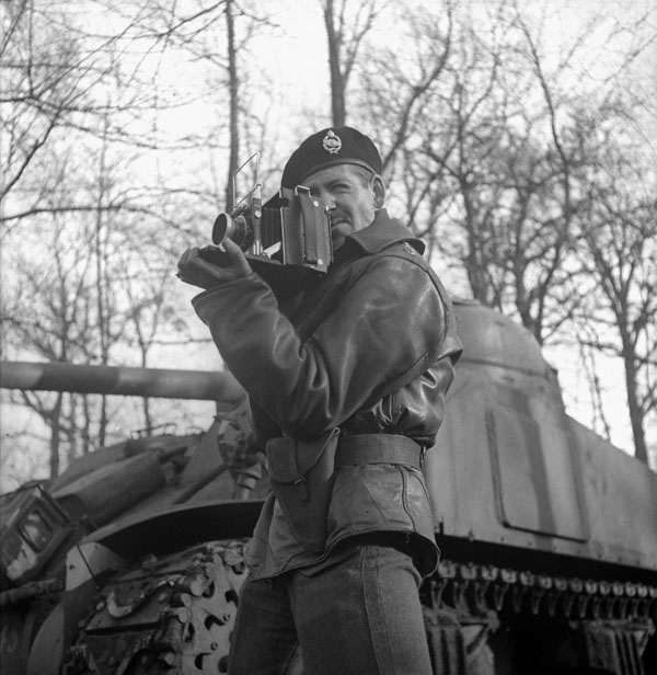Lieutenant  H. Gordon Aikman of the Canadian Army Film and Photo Unit, holding an Anniversary Speed Graphic camera.
