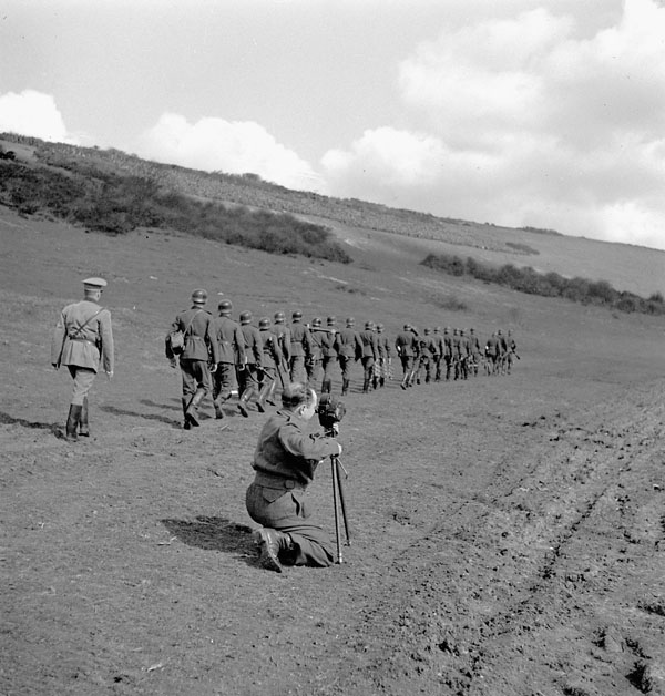 Sergeant Alan Grayston of the Canadian Army Film and Photo Unit filming a Canadian demonstration of German infantry tactics, Polegate, England, 28 March 1943.